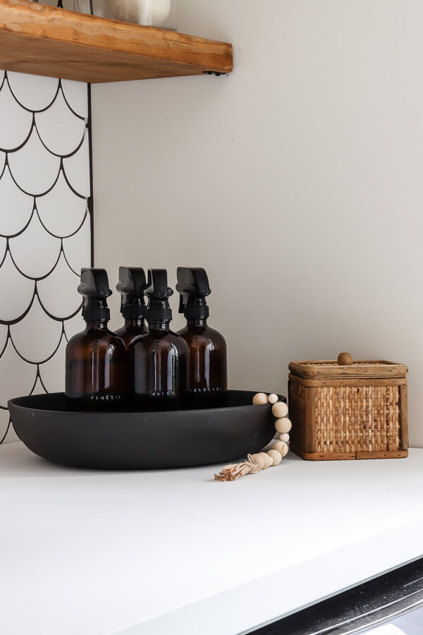 amber glass bottles in a black bowl with sherwin williams alabaster white walls and white mermaid tile backsplash