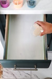 womans hand trying to do paint pouring in a white drawer