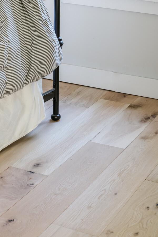 engineered white oak floors closeup with black metal bed