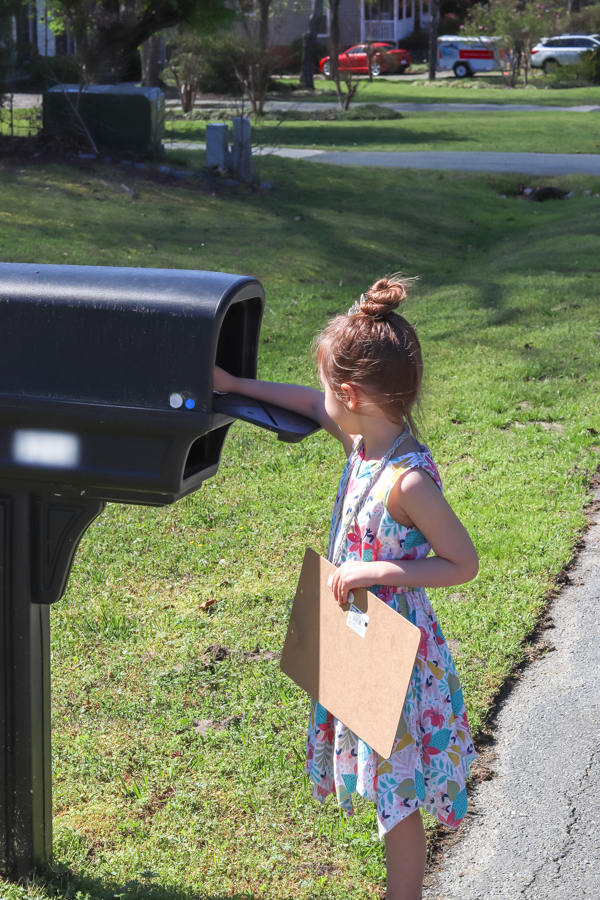 little girl putting love bunny neighbor gift in mailbox