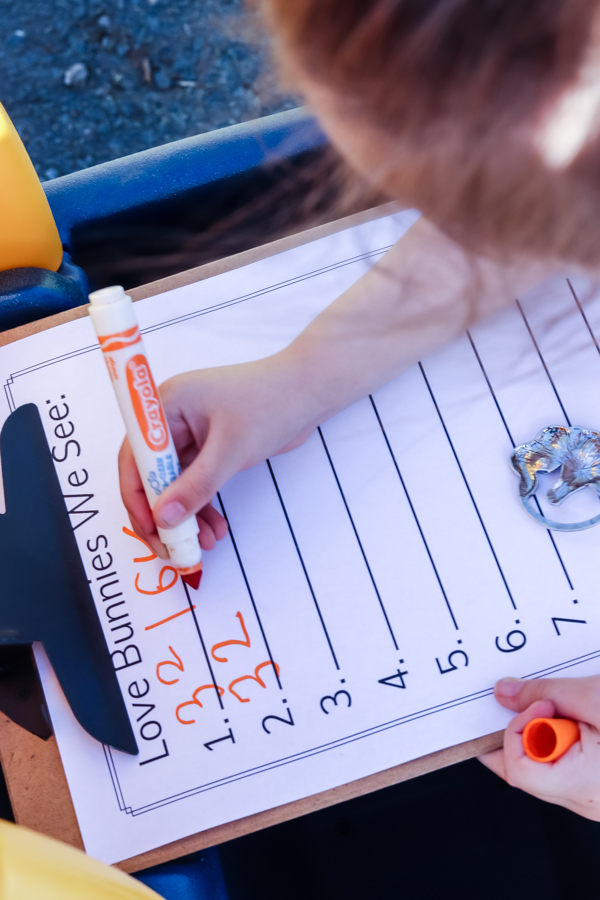 little girl writing house numbers for neighbor gift