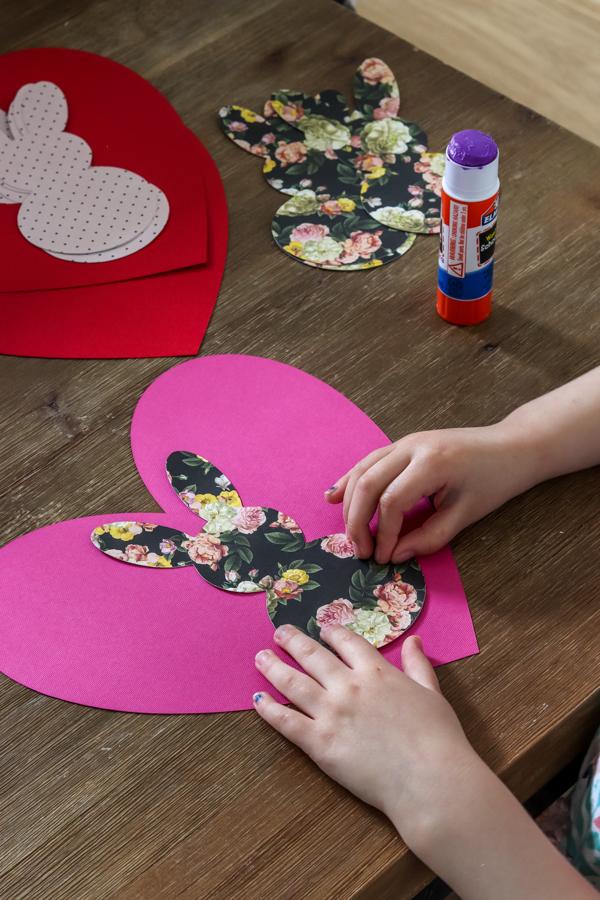 little girl gluing flower bunny on heart