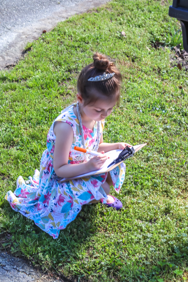 little girl in grass writing on clipboard
