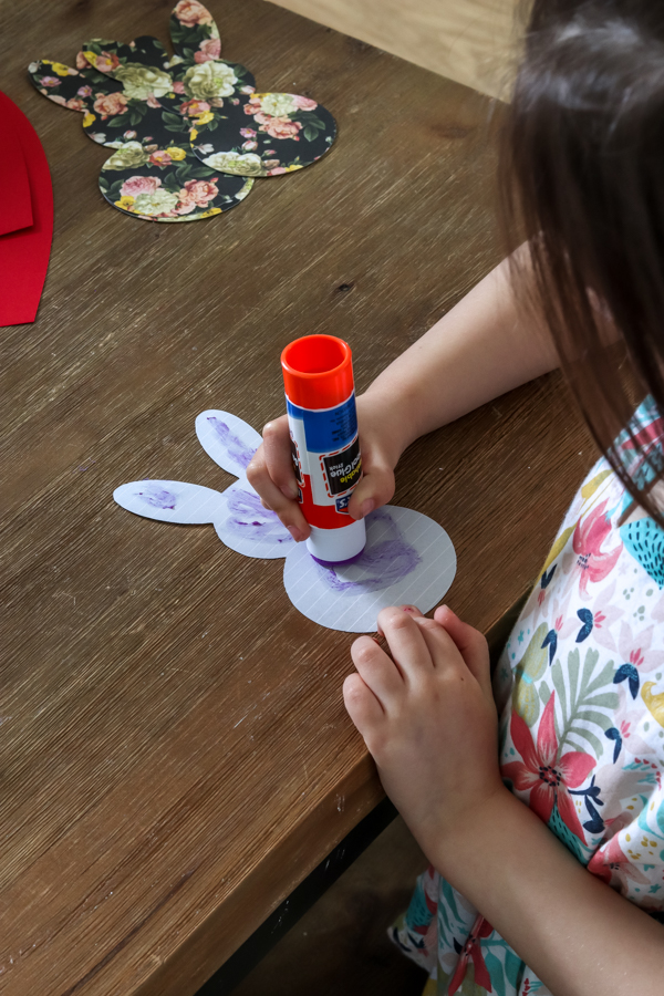 little girl putting elmer's glue on bunny paper