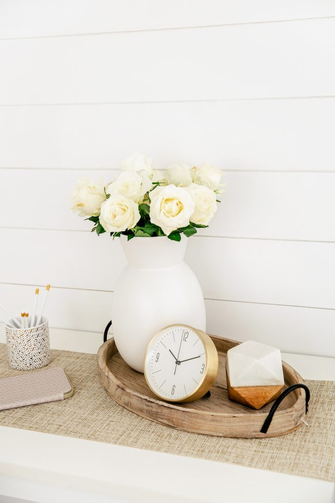white roses in white vase and on a tray with clock