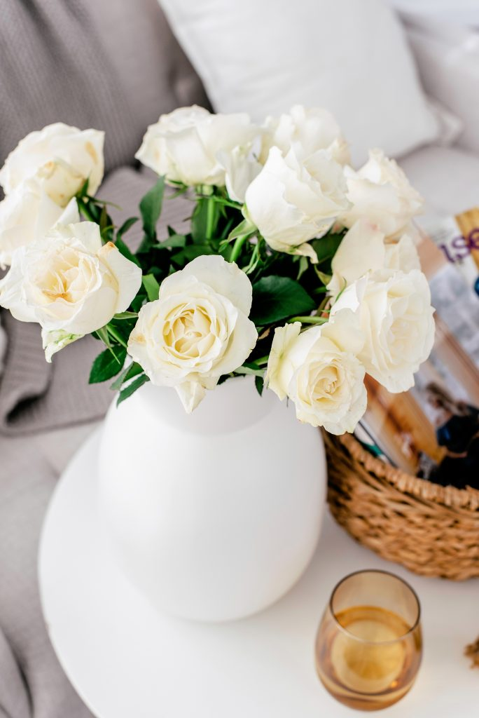 closeup of white roses in white vase