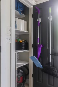 organized cleaning closet mops hanging on door