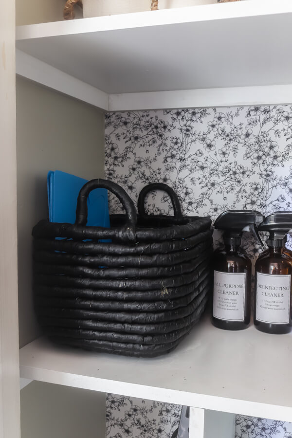 DIY homemade cleaners on shelf with black storage basket