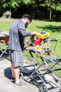 man cutting wood with miter saw