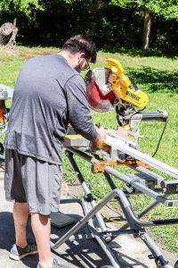 man measuring wood on miter saw