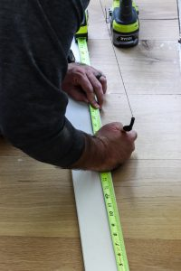 man marking wood with pencil