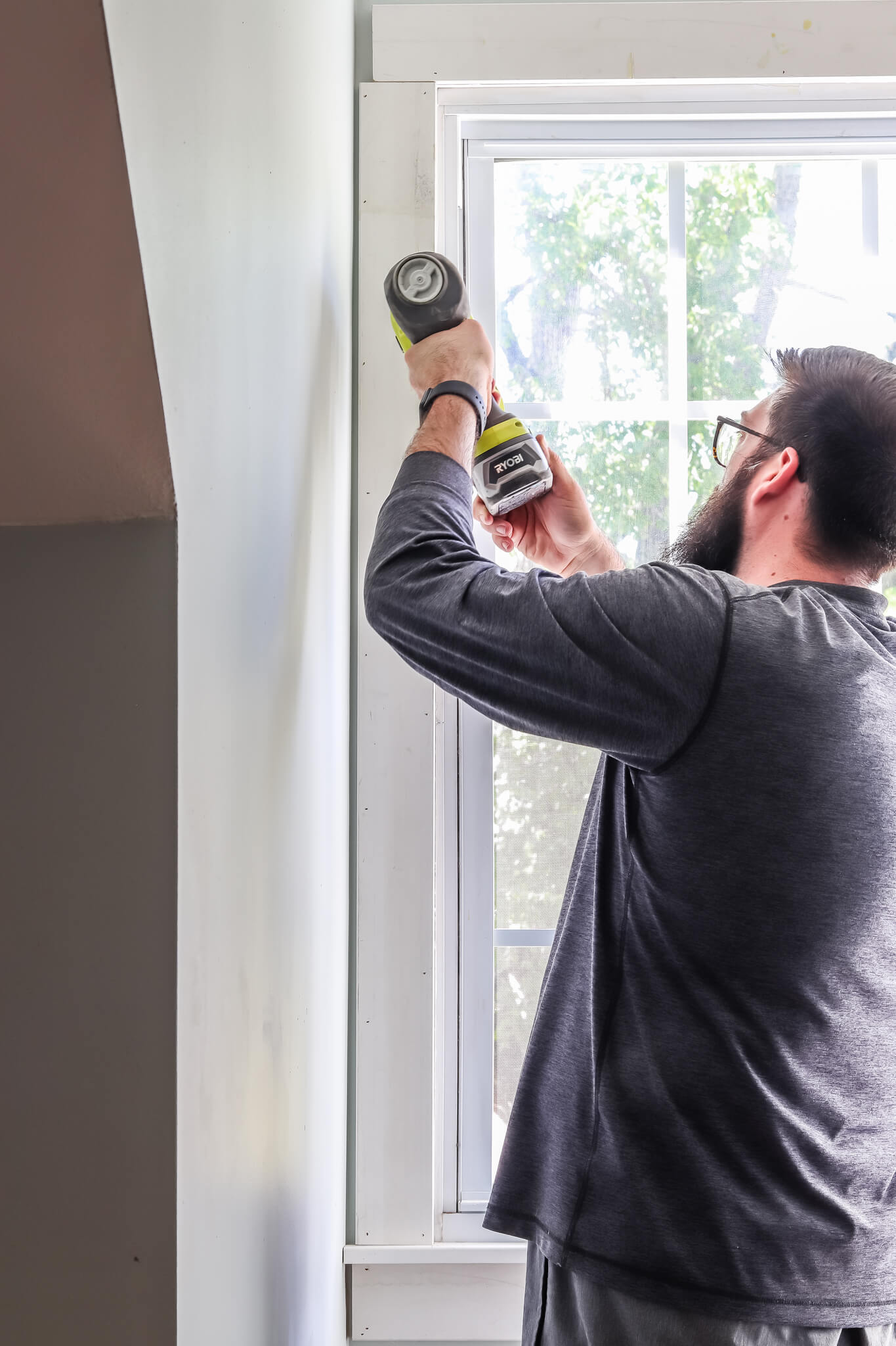 man using nail gun measuring window trim