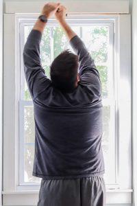 man using crowbar to pull off window trim header