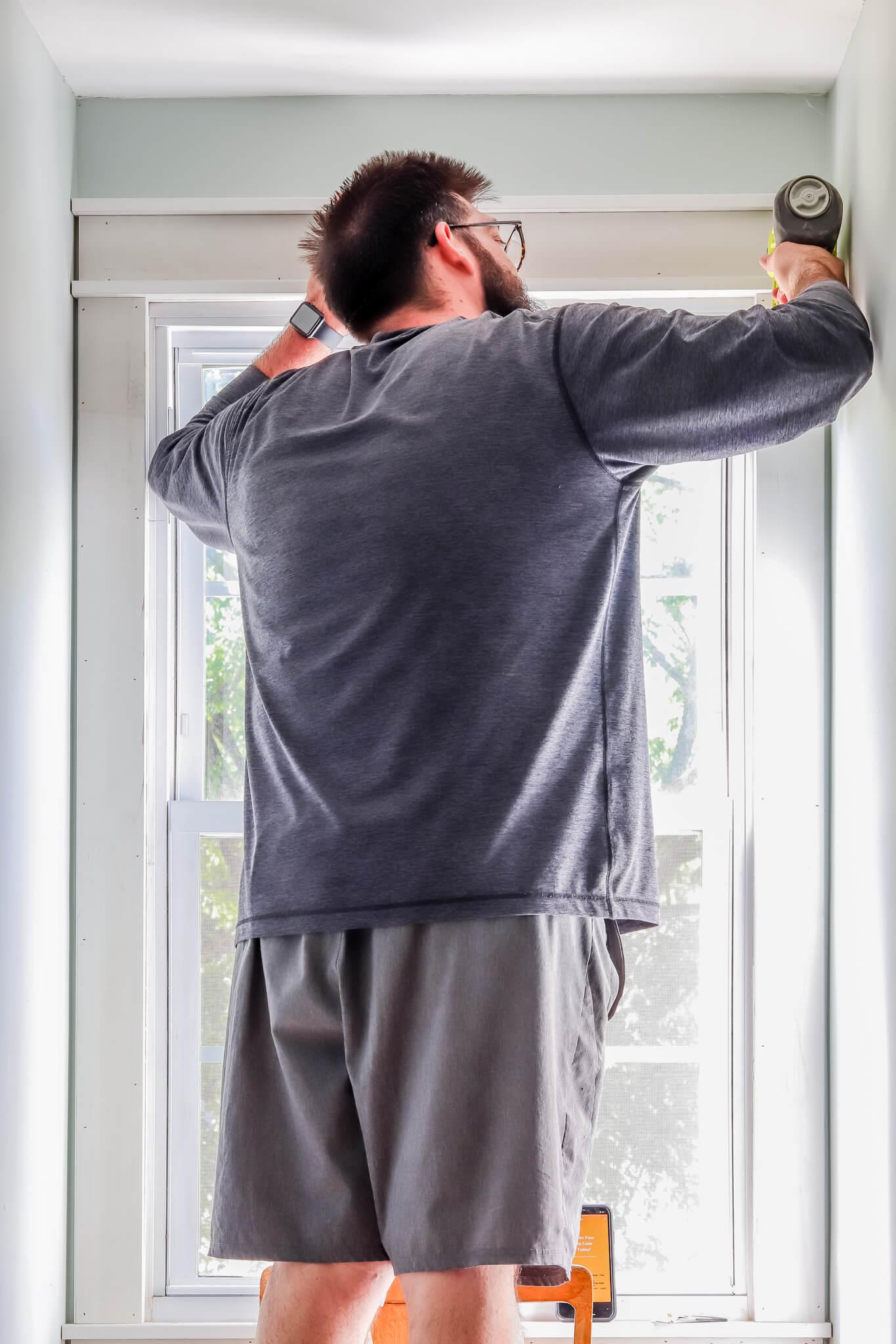 man using nail gun adding header to craftsman style window trim