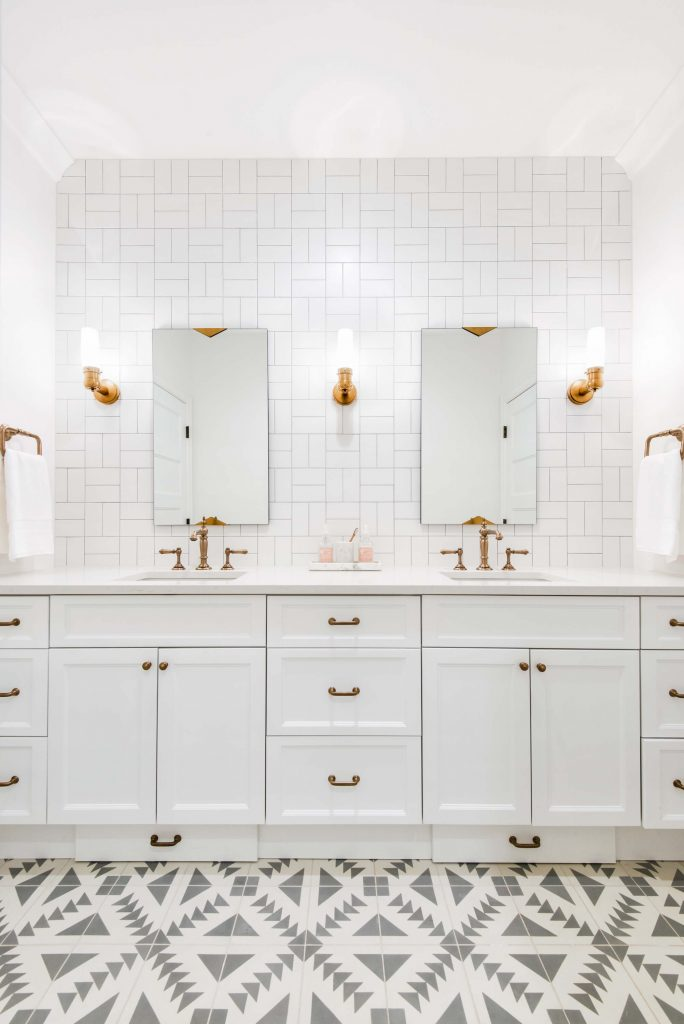 white vanity with white subway tile laid in cross hatch pattern