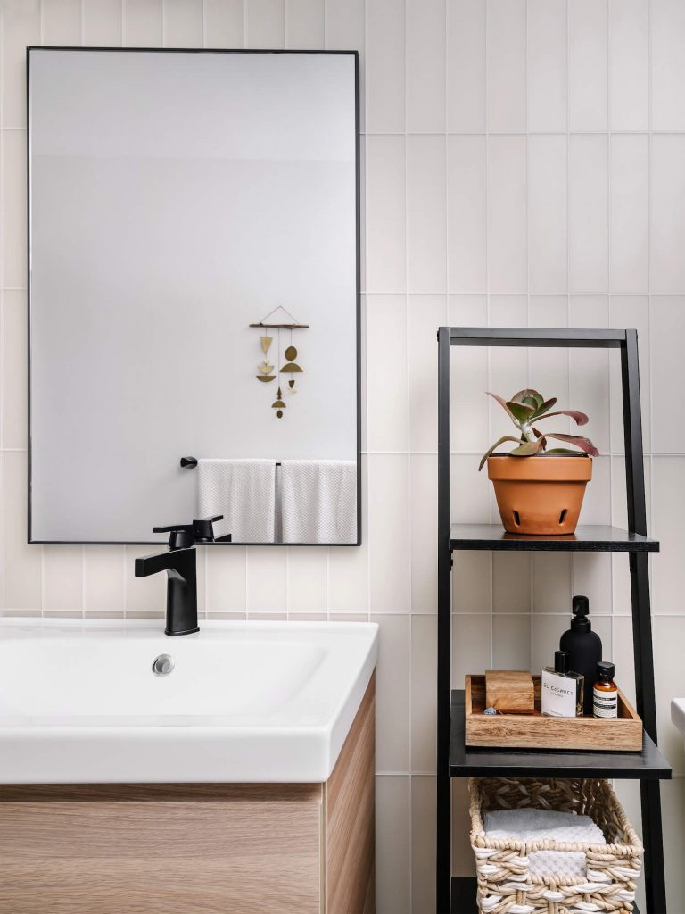 white and wood bathroom vanity with white vertical subway tile