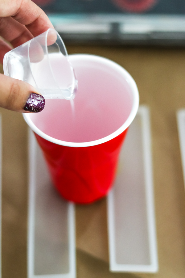 woman's hand pouring resin in to red solo cup