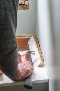 man removing drywall in a window seat in a dormer