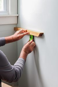 man using stud finder to hang up 2x2