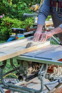 man's hands on table saw cutting wood