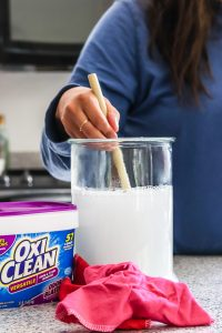 woman using wooden spoon to stir OxyClean and water