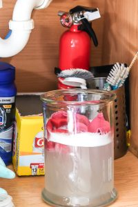 glass container with water and OxyClean under kitchen sink