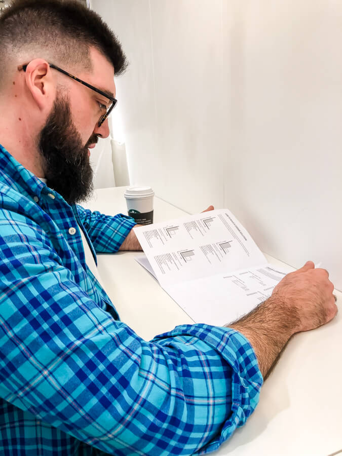 man with beard and glasses looking at a paper