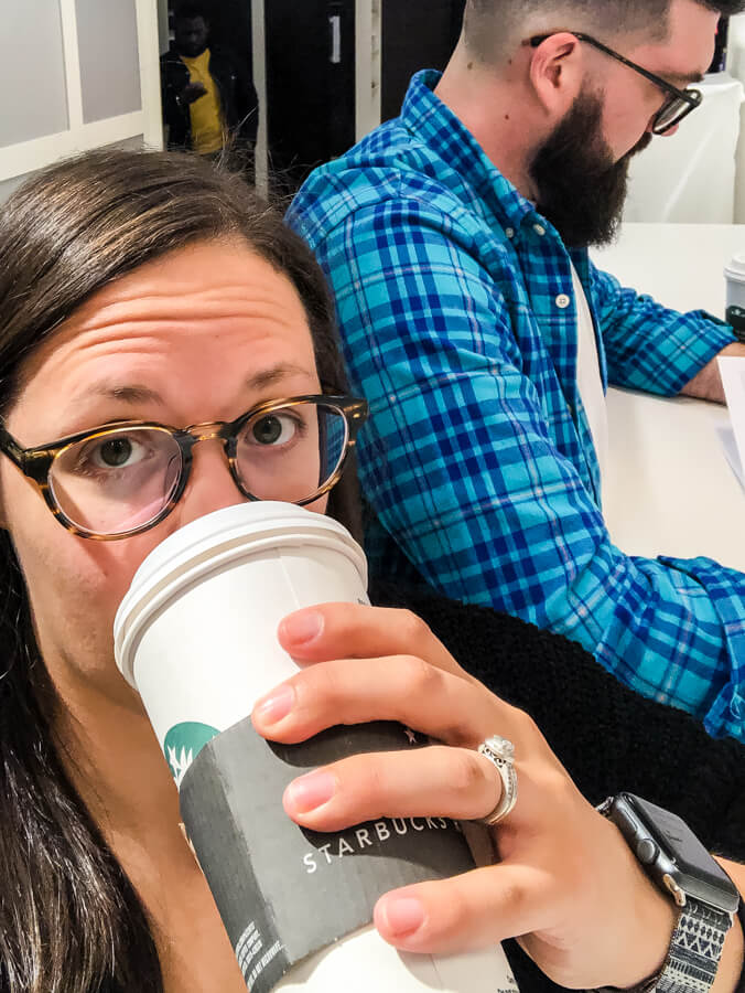 woman with glasses drinking starbucks with man with beard and glasses