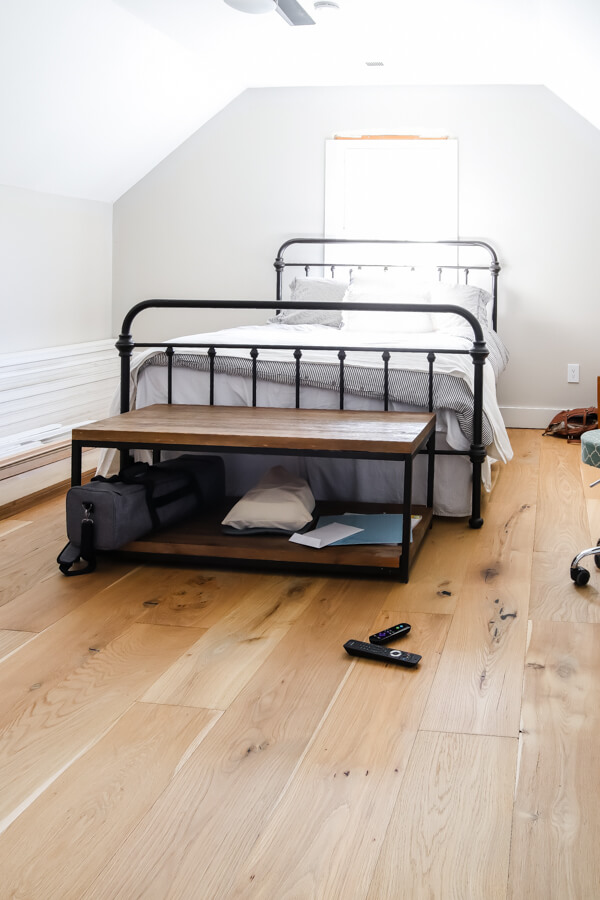 black iron bed with light wood floors
