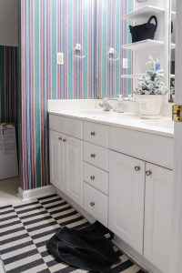 white vanity with white, green and red wallpaper