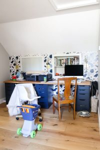 home office with navy desk and mismatched chairs