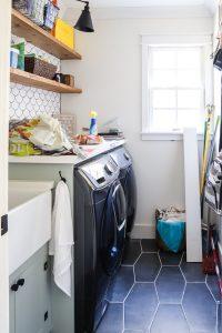 laundry room with dark floor and white backsplash