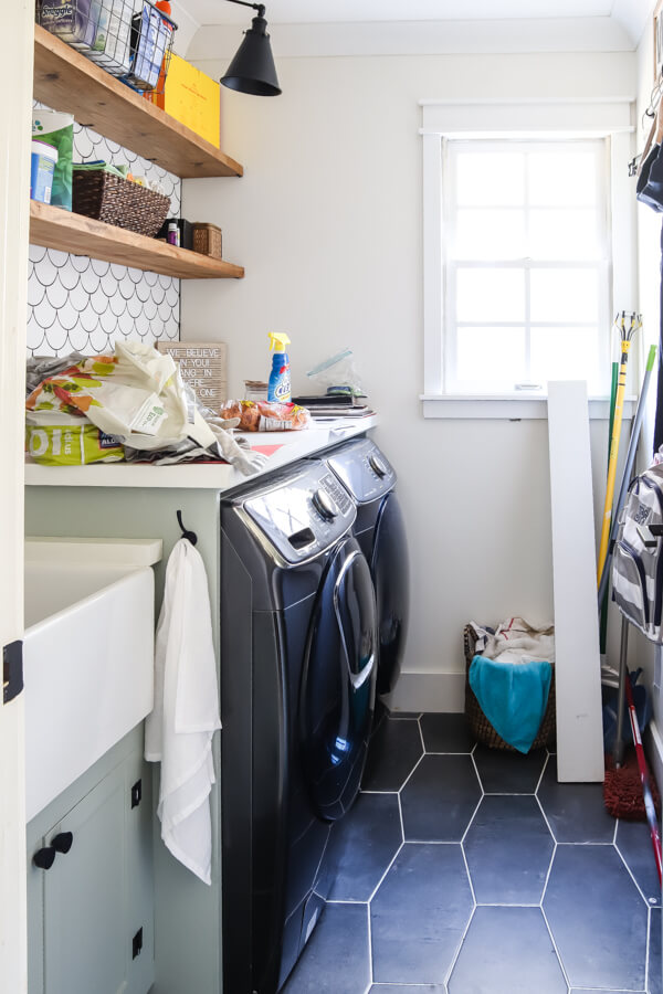 laundry room with dark floor and white backsplash