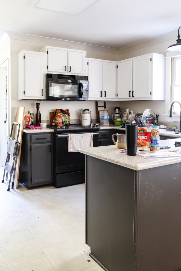 messy kitchen with gray lower cabinets and white upper cabinets