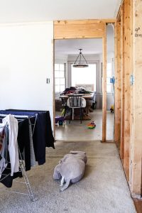exposed wall studs and laundry hanging up on drying rack