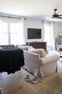 messy living room with laundry on drying rack