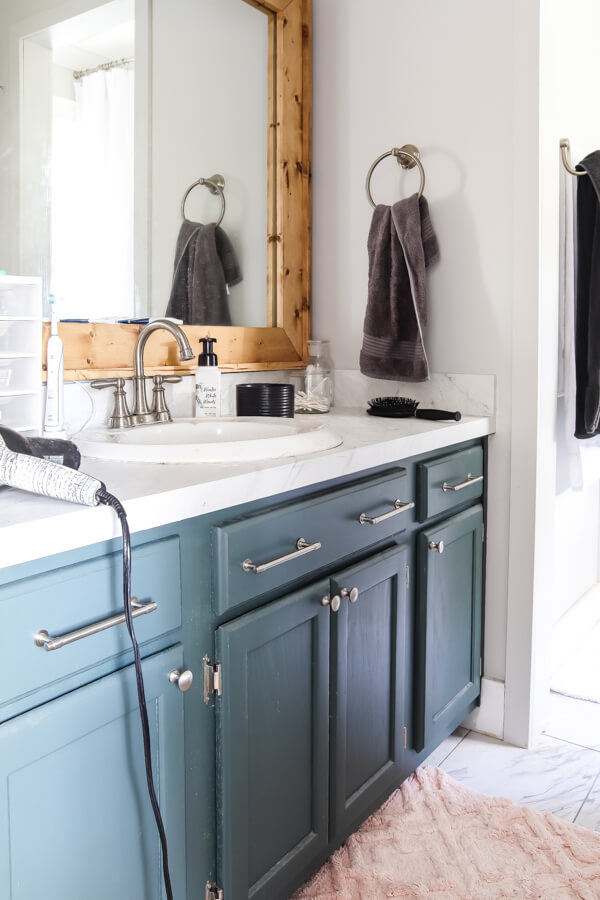 teal vanity with white marble top and wood framed mirror