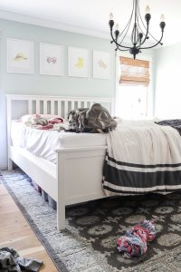 unmade master bed with backpack on it