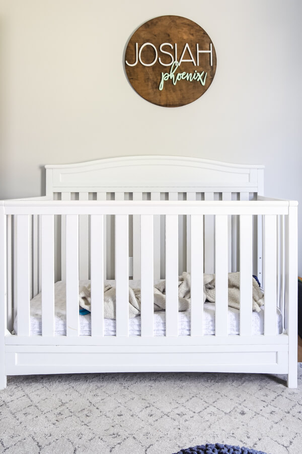 white crib with wood sign over crib