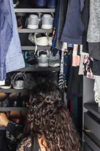 woman putting shoes on shelf in closet