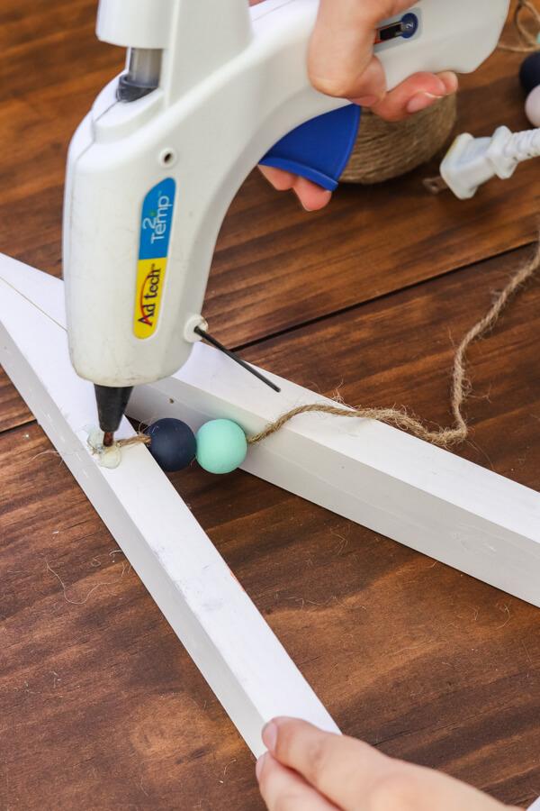 glue gun gluing twine to back of DIY wooden christmas tree