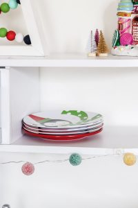 christmas plates stacked on white kidkraft kitchen