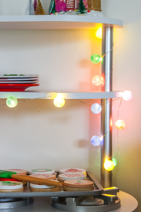 colored fairy lights lit up on white christmas kitchen