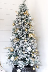 flocked christmas tree with few gold and white ornaments