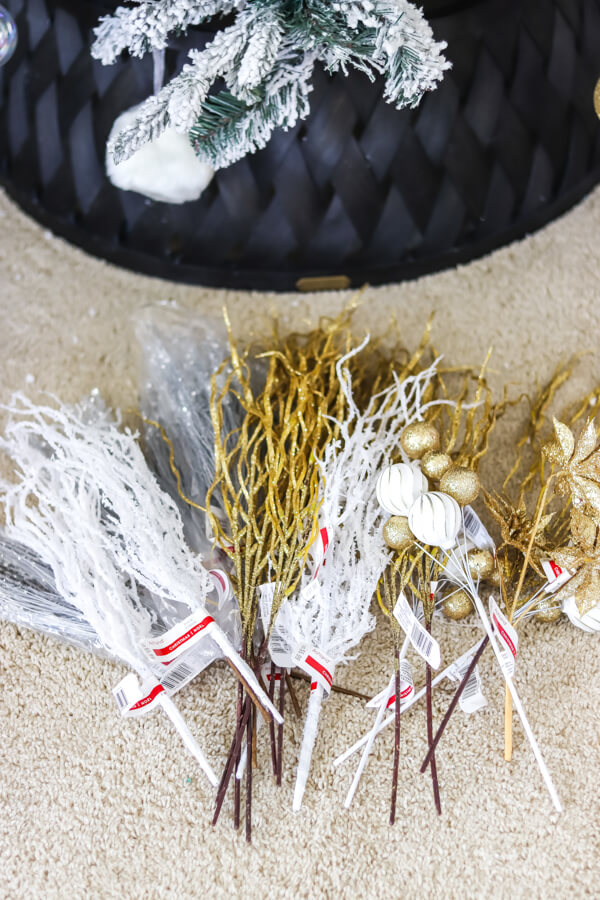 white and gold picks laying on the floor in front of a flocked christmas tree