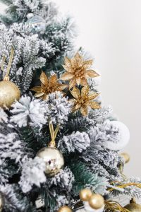 closeup of flocked tree with gold flower picks