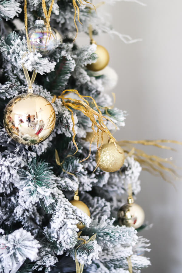 closeup of flocked christmas tree with gold pick