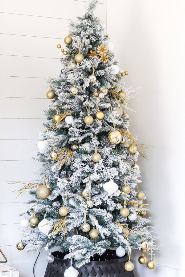 flocked christmas tree decorated with gold and white