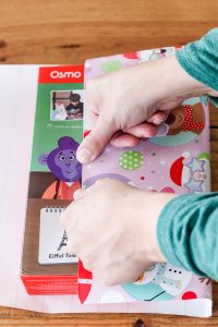 woman's hand taping wrapping paper on box