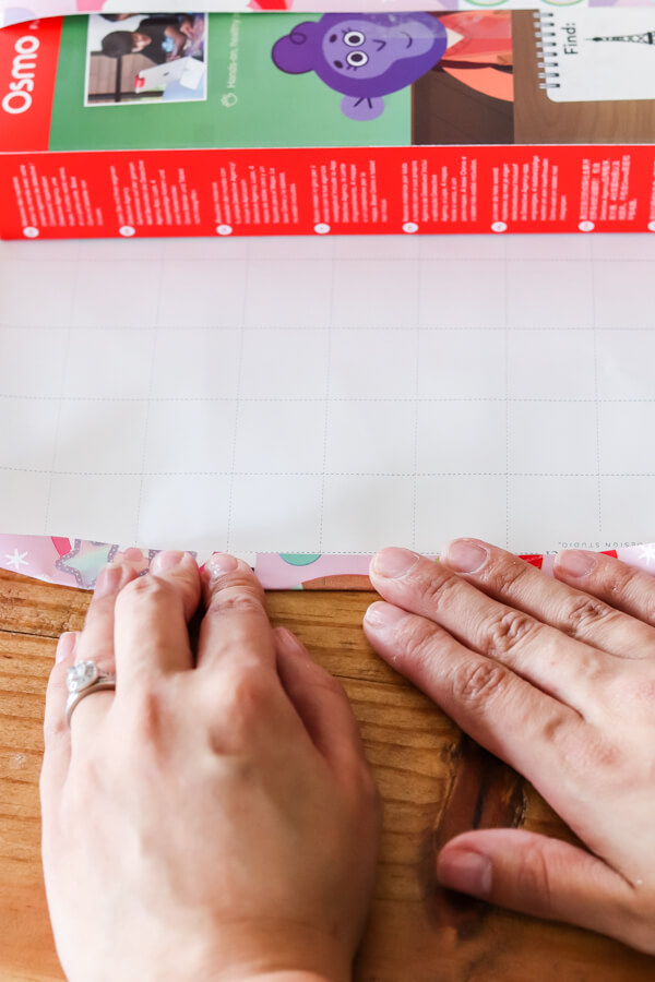 woman's hands folding wrapping paper to line up with grid